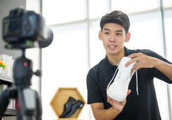 Social media influencer reviewing fashion shoe. Smiling young man vlogging about men's sports shoe and filming himself at home on a video camera.
